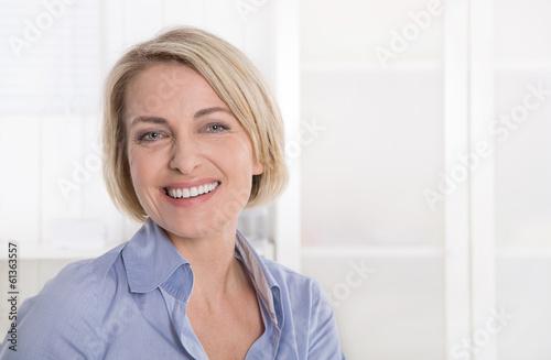 Fotografia  Ältere schöne blonde Frau - Portrait mit Hintergrund weiß blau
