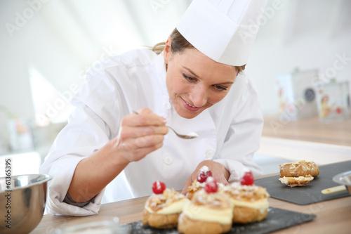 In de dag Bakkerij Professional cook spreading powdered sugar on cream puffs