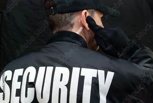 Security Guard Listens To Earpiece, Back of Jacket Showing Fototapet