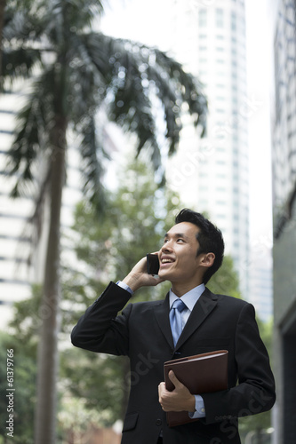Chinese business man using a smartphone. Poster