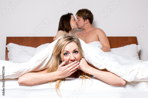 Photo  Cheeky young woman in a threesome in bed