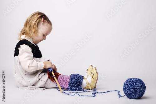 Fotografie, Obraz  cute little girl knitting scarf