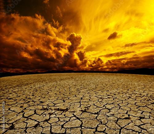 Poster Oranje Paisaje desertico.Cielo nuboso y suelo agrietado