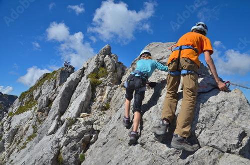 Spoed Fotobehang Alpinisme Kinder klettern am Fels im Klettersteig
