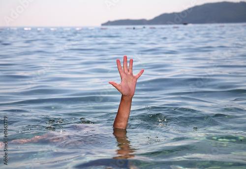 Fotografía  Ayuda concepto de una mano que se extiende fuera del agua en el mar