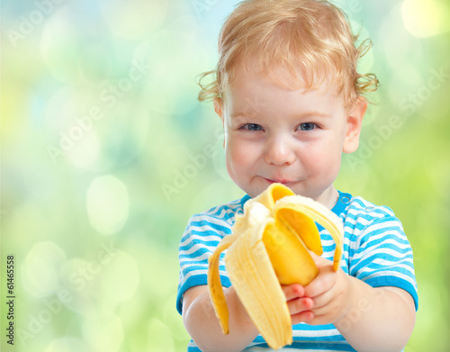 Fotografija  happy kid eating banana fruit. healthy food eating concept.