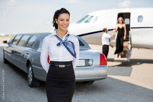 Attractive Airhostess Standing Against Limousine Et Jet Privé Poster Mural XXL
