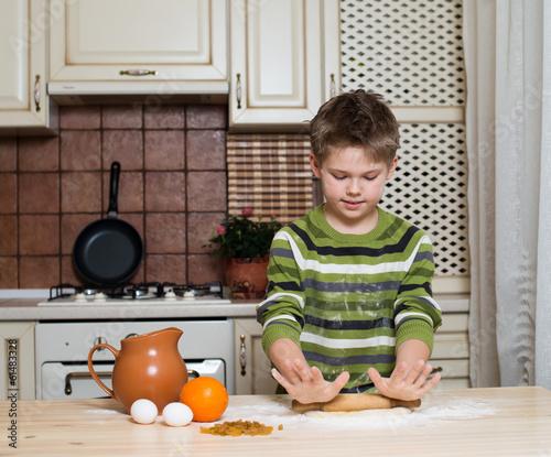Foto op Canvas Bakkerij A boy in the kitchen preparing the dough using rolling.