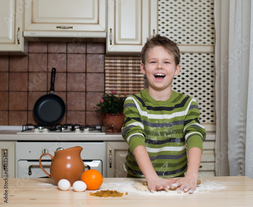 Foto op Canvas Bakkerij Laughing boy in the kitchen preparing the pastry using rolling.