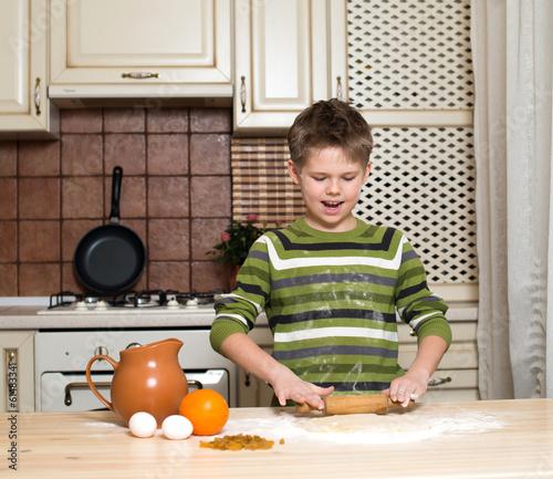 Foto op Canvas Bakkerij A boy in the kitchen making the dough using rolling.