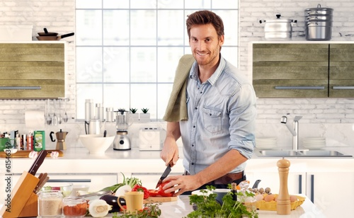 Fotomural Handsome man cooking in kitchen at home
