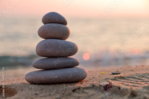 Photo sur Plexiglas Zen pierres a sable Stacked stones on the beach at sunset