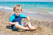 Little toddler boy playing with sand and stones on the beach
