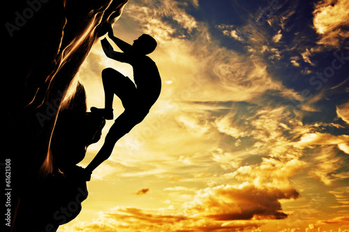 A silhouette of man climbing on mountain at sunset. Adrenaline