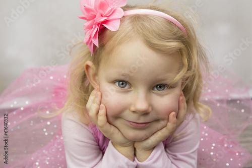 Mała baletnica z twarzą podpartą na dłoniach