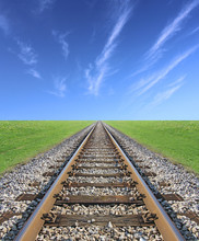 Railway Track, Green Grass And Blue Sky On The Horizon