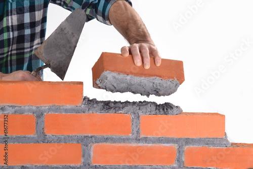 Constructor sujetando un ladrillo construyendo un muro. Canvas Print