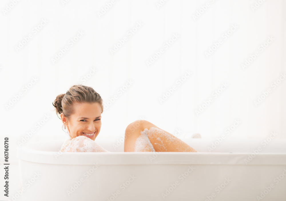 Fototapeta Happy young woman washing in bathtub