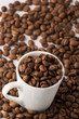 Roasted brown coffee beans in small espresso coffee cup