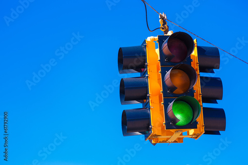 Photo  A green traffic light with a sky blue background