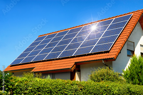Obraz Solardach auf einem Einfamilienhaus reflektiert die Sonne - fototapety do salonu