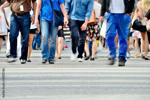 Fototapeta Motion blurred pedestrians crossing sunlit street obraz