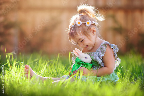 Photo  Cute little girl with a bunny rabbit has a easter at green grass