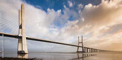 Photo  Vasco da Gama Bridge over the Tagus river at sunrise with cloudy