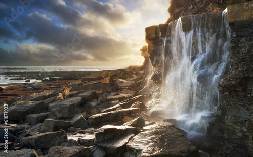 Garden Poster Black Beautiful landscape image waterfall flowing into rocks on beach