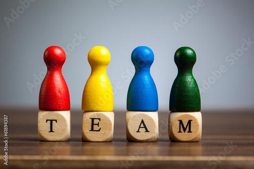 Fotografie, Obraz Four pawn figurines, team concept, table, grey background