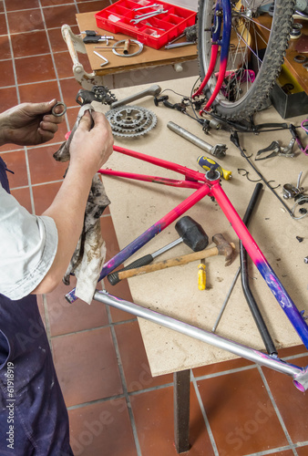 Photo Stands Asia Country Real bicycle mechanic cleaning bike parts