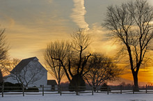 Rural Farm Barns And Trees At Sunset In Winter With Great Clouds