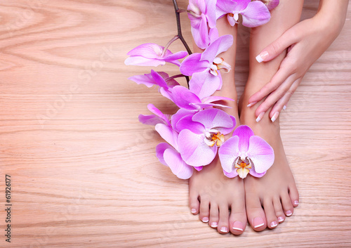 Poster Pedicure Foot care. Pedicure with pink orchid flowers on wooden