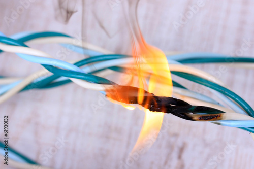 Valokuvatapetti Short circuit, burnt cable, on color wooden background
