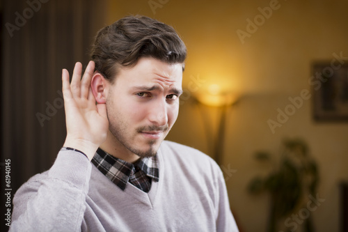 Foto  Handsome young man can't hear, putting hand around his ear