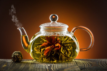 FototapetaGlass teapot with blooming tea flower on wooden table