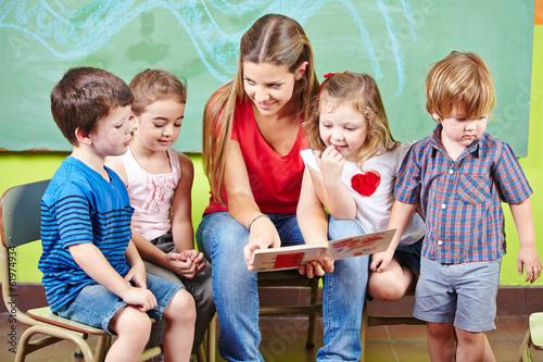 Fotografía  Kinder mit Erzieher lesen Buch im Kindergarten