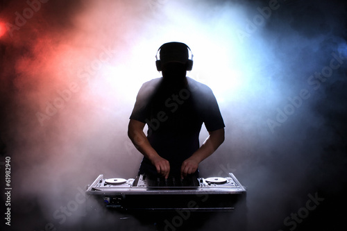 Fotografia  Disc jokey silhouette over illuminated smoke background