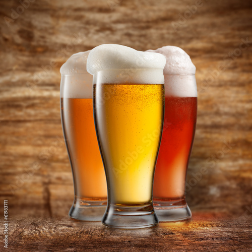 Foto op Canvas Alcohol Different beer in glasses on wooden background