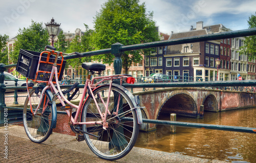 Photo  Pink Parked Bicycle Beside a Canal in Amsterdam