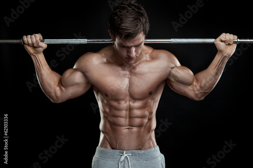 Fotografia  Muscular bodybuilder guy doing exercises with dumbbells over bla