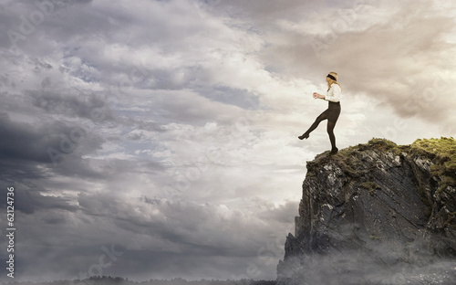 Obraz na plátne Risk, young businesswoman walking over the edge of the cliff
