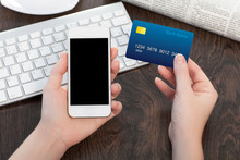 Female Hands Holding Phone And Credit Card Over The Table In Off