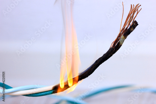 Valokuva  Short circuit, burnt cable, on color wooden background