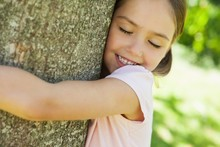Smiling Girl Hugging Tree With...