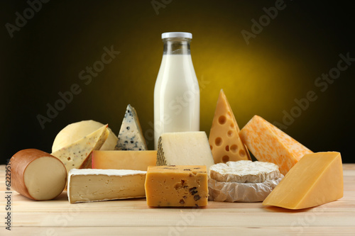 Poster Produit laitier Tasty dairy products on wooden table, on dark background