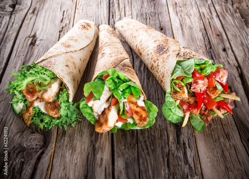 Fotografie, Obraz  Chicken slices in a Tortilla Wrap on wood.