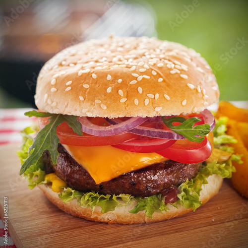 Fototapety, obrazy: Tasty burger with melted cheese on a sesame bun