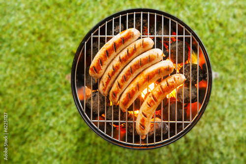 Aluminium Prints Grill / Barbecue Beef bratwurst grilling over a barbecue fire