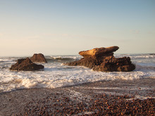 Seashore With Stones And Waves On The Background Of Sky